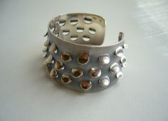 """A sterling silver bracelet with punched out 'scales' created by Norwegian designer, enamelist and jeweler Grete Prytz Kittelsen. Bracelet measures 1 1/2"""" wide and is signed Sterling, J. Tostrup, Norway. 59.0 grams."""