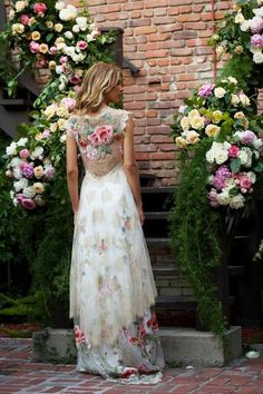 The Chantilly lace of the Heart's Desire wedding dress will cascade over your silhouette as pink and red peonies embroidered on flowing tulle dance across th...