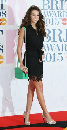 Michelle Keegan in a black lace dress carrying a box bright green leather bag