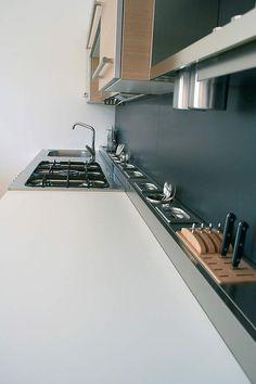 Un plan de travail optimiséLes cuisinistes savent exploiter le moindre recoin de nos cuisines. Jusqu'au plan de travail, qui peut intégrer une découpe pour une poubelle, des prises escamotables… Même le fond habituellement inutilisé peut devenir espace de rangement. En y implantant contre la crédence des logements encastrés (ici Ixina), ce que permet le vide sanitaire des meubles bas, on crée ainsi une zone pour les épices, couteaux, ustensiles.: