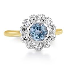 This mesmerizing Retro-era ring features a round aquamarine in a yellow gold setting with eleven old European cut diamond accents, creating a beautiful floral-inspired halo design (approx. 0.44 total carat weight).