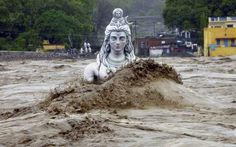 sixpenceee:  Statue of Shiva, nearly submerged in India's floodwater.