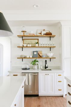 Home Interior Modern White kitchen cabinets brass pulls floating wood shelves industrial black light fixtures Kitchen Cabinets Decor, Farmhouse Kitchen Cabinets, Modern Farmhouse Kitchens, Cabinet Decor, Kitchen Shelves, Home Kitchens, Wood Shelves, Farmhouse Design, Floating Shelves