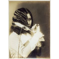 1920s • Woman Curling Hair  A young Japanese woman is waving her bobbed hairstyle.
