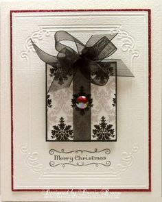 The beautiful black organza ribbon and bow totally make this card.  I barely noticed the designer paper or embossed background.  The bow and the rhinestone bling are all I need for this handmade Christmas card.