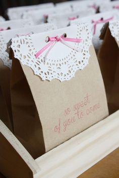 Easy, cheap, and adorable.  How to dress up a brown paper bag with a paper doily and a bit of ribbon.  (Paper bags can be printed in a printer, or stamped, but that's optional.)  And if I can't find a paper doily I could just use a rectangular piece of paper and punch it with a border paper punch.  I've also seen people flatten out a cupcake wrapper and then fold it in half over the top of a bag.