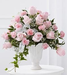 The FTD® Deepest Sympathy™ Arrangement is a wondrous presentation of grace and elegance to honor the life of the deceased. Pale pink roses and pink carnations are offset by baby's breath, variegated i
