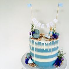 Pale blue and white striped Peter Rabbit first birthday cake for baby shower or christening. Cake bunting, edible flowers, pale blue macarons and meringue kisses