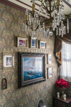 The wallpaper and sheer curtain fabric are the same ones used in Disneyland's Haunted Mansion. The vintage 1920s chandelier is a smaller version of the one Disney Imagineers installed in the 1960s. Carrie collected the lenticular changing portraits from eBay.