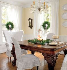 White Done Right White slipcovers unify the dining room chairs. A simple fir wreath on each window adds a touch of elegance.