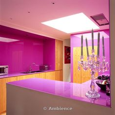 Ambience Images   A modern pink kitchen with wooden units and purple  work tops with a glass candelabra holder in the foreground.