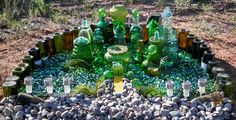 Fairy Emerald City--Collected green glass 'stuff' from Goodwill. Used E6000 to attach some of the glassware. Used old wine bottles for the outside wall--then LOTS of green glass balls from Dollar Store for the 'land' around the buildings. The teeny-tiny bricks I ordered from Amazon and painted them yellow!