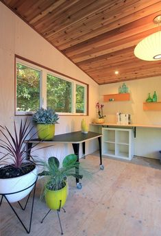 Modern home with end tables, console tables, pendant lighting, ceiling lighting, accent lighting, medium hardwood floor, bar, table, kitchen, beverage center, wood counter, and wood cabinet. The interior of the shudio has a ceiling of western red cedar and whitewashed ash walls. Furniture is flexible to host a variety of functions. Photo 2 of The Shudio