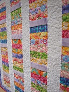 Simple and beautiful! I like how they didn't quilt through the solid purple blocks to make them pop.