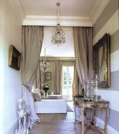 large baseboards - crown molding - hidden curtains as room divider - striped accent wall