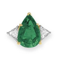 AN EMERALD AND DIAMOND RING, BY CARTIER   Set with a pear-shaped emerald, weighing approximately 8.37 carats, flanked on either side by a trillion-cut diamond, mounted in platinum and 18k gold  Signed Cartier
