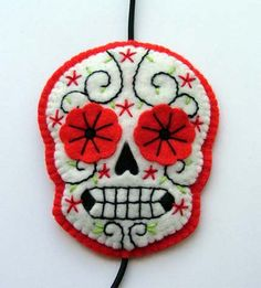 Day of the Dead Headband in a Red Sugar Skull Design.  Hand stitched and hand embroidered.  Made from several layers of felt, making the headband light and pliable.  The actual skull measures approx. 9cm x 7cm.  Attached to black elastic.
