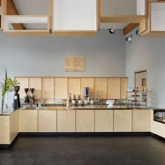 A display system made of stacked and suspended wooden boxes forms a signature feature in this new Blue Bottle cafe, which occupies part of a 1920s brick building in downtown San Francisco.