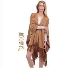 Camel Fringe Poncho Sweater Super chic fringe poncho. Great addition to any wardrobe. Loose fitting. Great looking fringe on the bottom. Just in from Tea and Cup designs. Would look great with your favorite skinny jeans or leggings! Tea n Cup Sweaters Shrugs & Ponchos