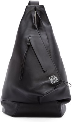 Leather crossbody backpack in black. Single shoulder strap at top. Silver-tone hardware. Inset zip closure at bag throat. Logo print in white at bag face. Zip pocket at side. Unstructured interior compartment. Tonal stitching. Approx. 15