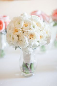 Ivory garden roses, white ranunculus, and ivory spray roses wrapped in ivory ribbon with the stems showing.