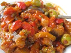 Vegan Sicilian Soul Food  2 small eggplants, diced  1 cup of green pitted olives  Half cup of capers  2 celery stalks  1 medium white onion  1 large red pepper  2.5 cups of diced tomatoes (or 1 can of crushed tomatoes)  A handful of pinenuts  1/3 cup of white vinegar  2tbsp sugar  Salt  Enough olive oil to sauté the veggies in.  #caponata #sicilianrecipes #sicilia #sicily