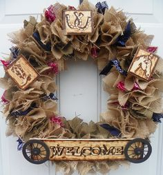 Burlap wreath with bandanas, wagon wheels, and signs that I made by drawing then burning them into the wood.