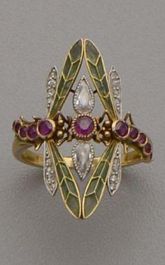 An Art Nouveau gold, plique-à-jour enamel, diamond and ruby ring. Designed as two dragonflies with green plique-à-jour enamel wings set with diamonds, the central element set with diamonds and rubies. With maker's mark CA.