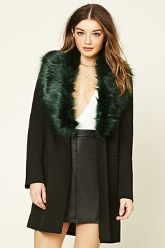 A woven coat featuring a removable faux fur lining, front snap-button closure, two front mock slit pockets, and long sleeves.