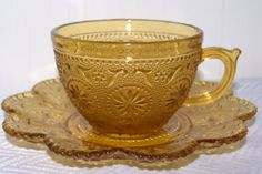 Beautiful amber glass vintage tea cup with saucer is has a floral and bubble pattern with scalloped edges on the saucer. Its possibly an Indiana