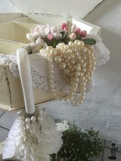 Romantic flowers and pearls in a very old white painted shabby chic sewing table so beautiful