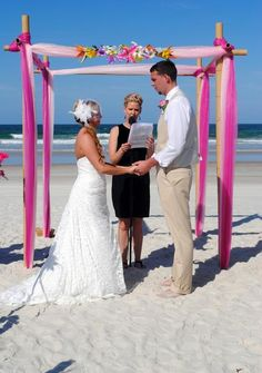 this fuschia and pink wedding canopy on the beach is perfect for your destination wedding by elitebeachweddings.com
