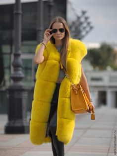 long yellow sleeveless fox fur coat