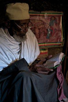 """Old Ethiopian Priest living in troglodyte room in rock hewn churches cluster, Lalibela, Ethiopia"""