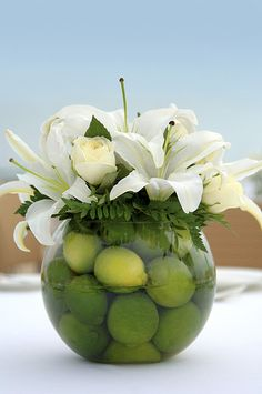 Centerpiece of small bowl filled with limes with white lillies and roses