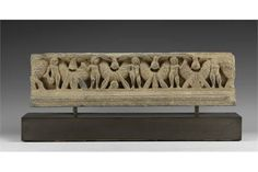 3rd-4th century AD. A schist frieze with a line of putti carrying flowering garlands, between cor