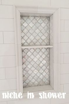 Arabesque tile, light grey grout, oversized white subway tile niche in shower