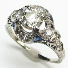 Gothic Rosette Ring:  Points of bright blue sapphire fold upward, creating a quatrefoil form that embraces the center diamond. Platinum scrolls and tendrils add support from below, and diamond accented petals grace the shoulders. Ca. 1920.  Maloys.com