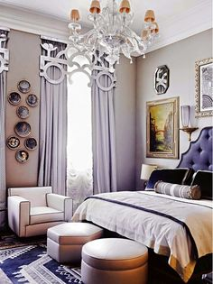 This cream and navy bedroom includes a large glass chandelier, patterned rug, luxe floor to ceiling curtains, vintage wall art, and two leather ottomans with a leather armchair.