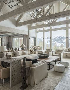 Neutral Rustic Interiors. Neutral rustic living room with vaulted ceiling and exposed whitewashed beams and trusses and floor to ceiling win...