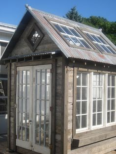 Old windows and wood pallets equal a cool new greenhouse/potting shed!