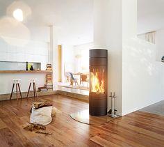 """Der Kaminofen """"elements rund"""" mit großzügiger 180°-Tür setzt nicht nur das Flammenspiel, sondern auch den Lieblingsplatz zu Hause gekonnt in Szene. Aufgrund seiner schlanken Silhouette und des großen Sichtfensters eignet sich der zeitlose Rundofen hervorragend als Raumteiler. Die Brennkammer ist zudem optional drehbar."""