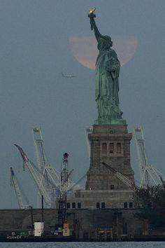 La Estatua de la Libertad con la superluna detrás entre nubes, en imagen tomada desde un avión que se acercaba al aeropuerto de Newark en Nueva York, el domingo 23 de junio de 2013. (AP Foto/Julio Cor