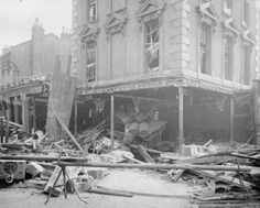 A general view of the damage to the Eaglet public house, on the corner of Seven Sisters Road, London, following an air raid. A 50 kilo bomb was dropped during a raid on the night of 29- 30 September 1917. Timber and debris litters the street, and wooden blinds hang broken from the windows. In the centre of the photograph can be seen a pile of beer barrels which have slipped down from their shelving.