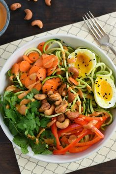 Zucchini Noodle Bowl with Spicy Cashew Sauce - Spiralized zucchini topped with carrots, red pepper, cilantro, a soft-boiled egg and an Asian-inspired spicy cashew sauce.