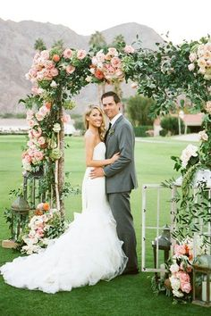 ceremony arch covered with peach and coral flowers and lush greenery - Deer Pearl Flowers