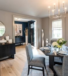 Complementary colors, carried from one room connected to another, create a pleasing flow. Here, a moody blue accent wall in the foyer is seen from the subdued gray dining room. Subtle hints of blue are repeated in the dining chair fabric and place settings, as well as in the cabinetry of the adjacent working kitchen. #stickleyaudi #Circalighting #dickshanley