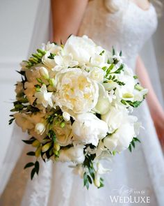 Elegant white bouquet with touches of greenery.