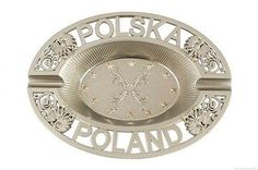 "Frosted silver colored metal ashtray with ""POLSKA"" and ""POLAND"" lettering on the rim. Featured on either side of the country's name is the Polish White Eagle with gold colored talons and crown. At the"