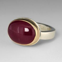 """The """"King of Gems"""", rubies have been treasured for thousands of years, and continue to be objects of desire. A sterling silver and 14k yellow gold, smooth oval African Ruby on skinny smooth band. <br><br>Stone measures approximately 13.1mm x 16.5mm<br><br>Size 6.5<br><br><div><b>Special Sizing:</b></div><div>There is no charge for a first time sizing. </div><div>Delivery for a special sizing is 4 weeks"""